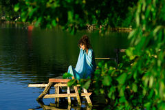 Extremely beautiful girl with perfect professional hairstyle sit near water Stock Photography