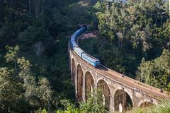 Nine Arches Bridge and blue train in Sri Lanka, Ella. The Nine Arches Bridge Demodara is one of the iconic bridges in Sri Lanka stock image