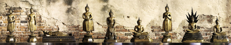 Nine attitude of Buddha statues with cement and brick wall background. Nine attitude of Buddha statue with cement and brick wall background panorama stock photos