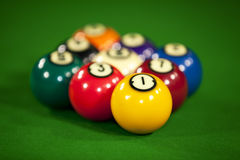 Nine billiard balls. On a billiard table with the focus on the yellow ball number one Stock Images