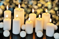 Nine burning candles on a dark shiny background Stock Photos