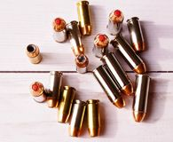 Nine 40 caliber hollow point bullets and eight 44 special bullets with red tips. Shown on a wooden background, shot from above stock photos