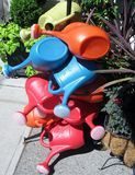 Nine colored plastic watering cans. Stock of colored plastic watering cans Royalty Free Stock Images
