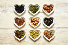 Nine colorful tea sorts in heart shaped bowls. Top down view on nine colorful mild and spicy culinary tea sorts filled up inside cute little heart shaped royalty free stock image