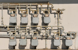 Nine gas power meters. Nine natural gas power meters and pipes on brown wall Royalty Free Stock Photos