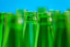 Nine green bottle necks, in center one bottle. Nine green bottle necks on blue background, in center one bottle in focus Stock Photos