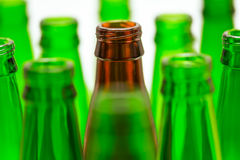 Nine green and one brown bottles. Stock Photos