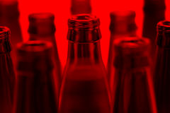 Nine green and one brown bottles shot with red light. Royalty Free Stock Image