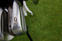 Nine iron and golf clubs on the green Royalty Free Stock Images