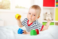 Nine month old baby lying in the bed on white blanket. Cute boy playing with cubes Royalty Free Stock Image