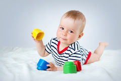 Nine month old baby lying in the bed on white blanket. Cute boy playing with cubes Stock Images