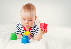 Nine month old baby lying in the bed on white blanket. Cute boy playing with cubes Stock Photography