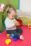 Nine months old baby girl sitting on the floor Stock Photos