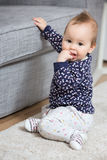 Nine months old baby girl sitting on the floor Stock Images