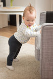 Nine months old baby girl standing on her feet Stock Photography