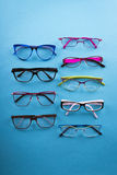 Nine pair of lasses on the blue backgraund. Nine pair of glasses different forms of colored spectacles are rows on a blue background royalty free stock photography