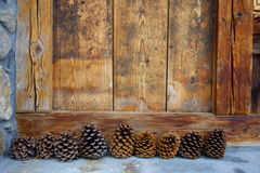 Nine pine cones and wood. In front of a chalet Stock Image