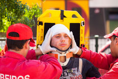 NINE, PORTUGAL - APRIL 12, 2014: Emergency crew immobilizes vict. Im with a cervical collar in a stretcher during a simulated train accident Stock Photo