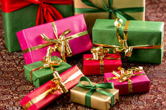 Nine Presents for any Occasion. Nine gift boxes with bows in gold, green and red. Shallow depth of field. Richly textured cloth. Fit for any gift-giving event Stock Photo