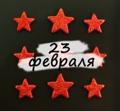 Nine red stars on black background. Flat lay. View from above. Day of the defender of Fatherland. The day of Soviet and Russian. Armies. Russian text royalty free stock images
