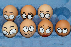 Nine sad  frightened egg faces in blue panel Royalty Free Stock Photography