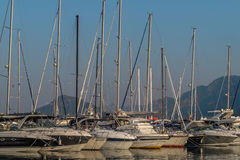 Nine sailboats in a harbor. Nine small white sailboats without sails in a harbor. Sky is clear and mountains are seen in a haze. Photo was taken in a morning Stock Photography