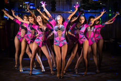 Nine showgirls in purple costumes with raised hands perform Royalty Free Stock Images