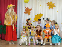 Nine small childrenand adult woman dressed in carnival costumes Royalty Free Stock Image