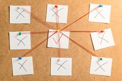 Nine white stickers for notes with x and v marks rewound on a ca. Rdboard background on whole frame royalty free stock photo