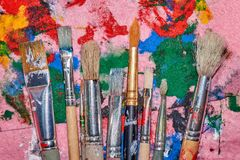 Nine worn out brushes of different sizes on the colorful pink palette royalty free stock images
