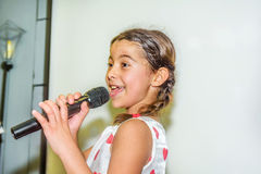 Nine year old girl singing with microphone.  Royalty Free Stock Photo