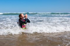 Young girl in surf at Makorori Beach, near Gisborne, New Zealand. Nine year old red haired girl in surf,at Makorori Beach, Gisborne, New Zealand, on a clear royalty free stock photography