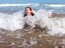 Young girl in surf at Makorori Beach, near Gisborne, New Zealand. Nine year old red haired girl in surf,at Makorori Beach, Gisborne, New Zealand, on a clear stock images