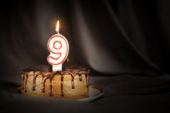 Nine years anniversary. Birthday chocolate cake with white burning candle in the form of number Nine. Dark background with black cloth stock photography