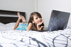 Nine years old child having fun using laptop at her bedroom Stock Image