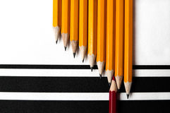 Nine yellow and one red pencil on structured paper. Nine yellow pencils with a black point and one red pencil with a red point laying on structured paper with Royalty Free Stock Images