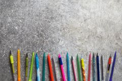 Nineteen colorful pens on grunge grey table background