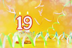 Nineteen years birthday. Cupcake with burning candles in the form of number 19. Bright yellow background with copy space royalty free stock photo