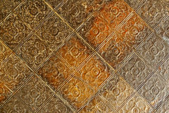 Nineteenth century embossed tin ceiling tiles. Background image of nineteenth century embossed ceiling tiles with an aged patina Royalty Free Stock Image
