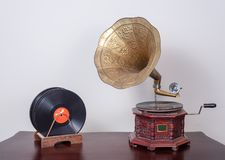 Nineteenth century phonograph gramophone and vinyl records on a wooden table and beige wall. Still life of a nineteenth century phonograph gramophone and vinyl Stock Images