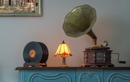 Nineteenth century phonograph and vinyl records on a wooden table and background of beige wall and hanged painting. Nineteenth century phonograph gramophone and stock photo