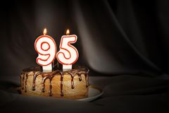 Ninety five years anniversary. Birthday chocolate cake with white burning candles in the form of number Ninety five. Dark background with black cloth stock images