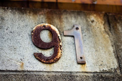 Ninety1. Old building number rusting away with time Stock Photo