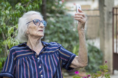 Ninety years old grandma taking a selfie with a smartphone in th. E backyard. Communications abstract stock photos