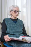 Ninety years old lady reading newspapers royalty free stock photo