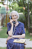 Ninety years old lady talking on the phone in the backyard Royalty Free Stock Photo