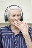 Ninety years old woman reaction to modern music. Grandma listeni. Ninety years old grandma reaction while listening to modern music. Grandma listening to music Stock Photography