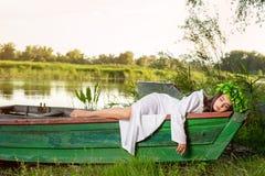 A ninfa com cabelo escuro longo em um vestido branco do vintage que senta-se em um barco no meio do rio fotos de stock royalty free