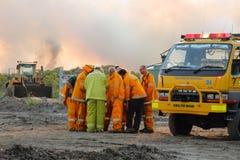 NINGI,澳大利亚- 11月9 :射击前面的消防队员乘员组dicussing的方法灌木火2013年11月9日在Ningi, Austra 库存照片