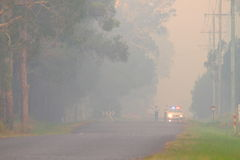 NINGI, AUSTRALIA - NOVEMBER 9 : Police holding cordon in front of bush fire front as it approaches houses November 9, 2013 in Ning Royalty Free Stock Images